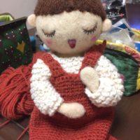 レンガ色のジャンパースカートを身につけた、お人形さん