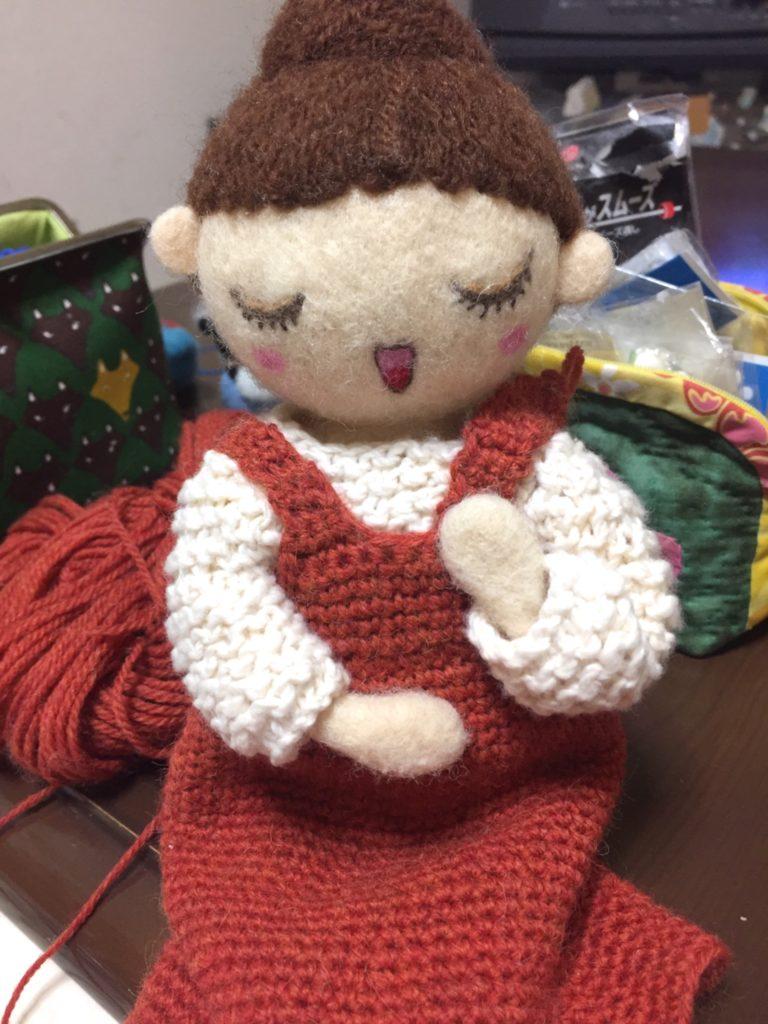 レンガ色のジャンパースカートを身につけた、お人形さん。